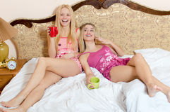 Portrait of two sexy pretty girlfriends having fun drinking tea holding red and green cups & looking at camera Stock Photography