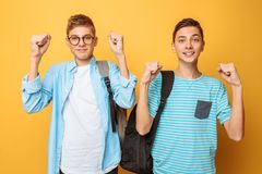 Portrait of two shocked teenagers, guys show victory gesture, on yellow background. Portrait of two shocked teenagers, guys show victory gesture royalty free stock photography