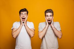 Portrait of a two shocked young men best friends. Looking at camera with mouth open over yellow background stock photo