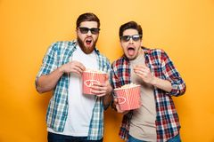 Portrait of a two shocked young men in 3d glasses. Eating popcorn while standing isolated over yellow background stock photos