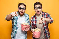 Portrait of a two shocked young men in 3d glasses. Eating popcorn while standing and pointing fingers at camera isolated over yellow background royalty free stock photography