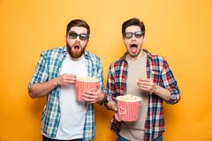 Portrait of a two shocked young men. In 3d glasses eating popcorn while standing isolated over yellow background royalty free stock photography