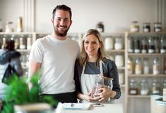 A portrait of two shop assistants standing in zero waste shop, looking at camera. A portrait of two shop assistants standing arm in arm in zero waste shop royalty free stock photos
