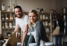 A portrait of two shop assistants standing in zero waste shop, looking at camera. A portrait of two cheerful shop assistants standing in zero waste shop royalty free stock images