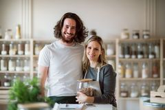 A portrait of two shop assistants standing in zero waste shop, looking at camera. A portrait of two shop assistants standing arm in arm in zero waste shop stock photos