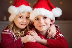 Portrait of two siblings in red Santa's hats Royalty Free Stock Photo