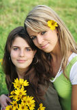 Portrait of two sisters. Outdoor portrait of two sisters with flowers stock photo