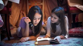Portrait of two cute sisters lying in tepee tent at bedroom and reading book with flashlight. Portrait of two sisters lying in tepee tent at bedroom and reading Stock Photography