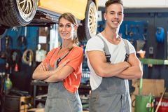 Portrait of two skilled auto mechanics looking at camera with confidence. While wearing gray overall in a modern automobile repair shop with experienced Stock Photography