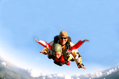 Portrait of two skydivers in action. Portrait of two tandem skydivers in action parachuting through the air Stock Photography