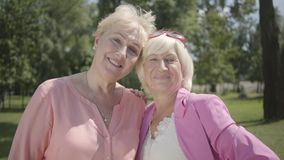Portrait of two smiling adorable women looking at camera smiling standing in summer park. Leisure outdoors. Mature. Portrait of two positive old women in pink stock footage