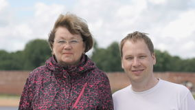 Portrait of two smiling adult woman and young man stock footage