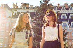Portrait of two smiling beautiful girls, teenagers 13, 14 years old, close-up, girls talking laughing and walking in summer city royalty free stock image