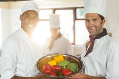 Portrait of two smiling chefs holding a bowl of vegetable Stock Images