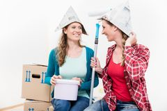 Two female friends renovating their new house. Portrait of two smiling female friends renovating their new house royalty free stock image
