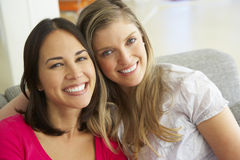 Portrait Of Two Smiling Female Friends On Sofa Royalty Free Stock Image