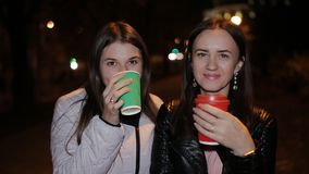Portrait of two smiling friends on the street in the evening with coffee in hand. stock video footage