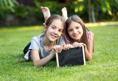 Portrait of two smiling girls lying on grass with chalkboard Royalty Free Stock Photography