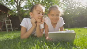 Portrait of two smiling girls lying on grass and using digital tablet. Two smiling girls lying on grass and using digital tablet stock footage