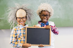 Portrait of two smiling school kids holding slate in classroom Royalty Free Stock Photos