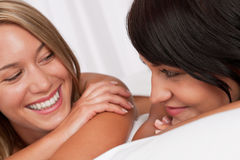 Portrait of two smiling women lying down in bed Stock Photo