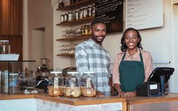 Two smiling African entrepreneurs standing behind their cafe counter. Portrait of two smiling young African entrepreneurs standing welcomingly together behind stock photos