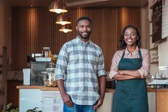 Two smiling African entrepreneurs standing at their cafe counter. Portrait of two smiling young African entrepreneurs welcomingly togetherin front of the counter royalty free stock photography