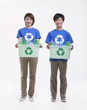 Portrait of two smiling young people holding recycling bins and wearing recycling symbol t-shirts, studio shot Stock Photo