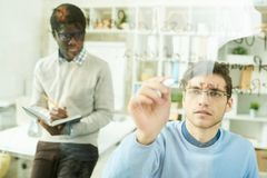 IT Developers Writing on Glass Wall. Portrait of two IT specialists writing formulas on glass wall in modern office, focus on young men wearing glasses, copy Royalty Free Stock Images
