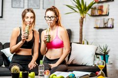 Sports women at home. Portrait of a two sports women friends sitting with fresh drinks on the couch after the training at home stock photos