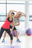Portrait of two sporty people stretching hands at yoga class Stock Image