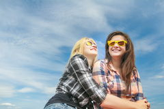 Portrait of two student friends wearing yellow mirror sunglasses Royalty Free Stock Images