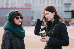 Portrait of two stylish and beautiful girlfriends standing on the middle of the city street. Portrait of two stylish and beautiful girlfriends standing on the Stock Photos
