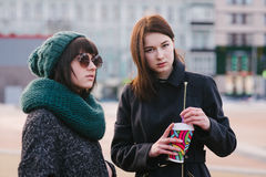 Portrait of two stylish girls friends are standing in the middle of the city. One girl is holding a coffee in another scarf and glasses Royalty Free Stock Photos