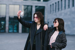 Portrait of two stylish women wearing hipster who are photographed on smortfon. Against the backdrop of the beautiful modern architecture Stock Photos