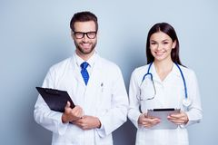 Portrait of two successful professional doctors workers in coats. Holding clipboard and digital tablet against gray background Stock Images
