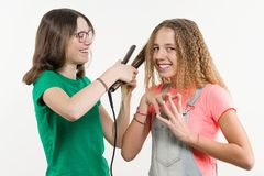 Portrait of two teenage girlfriends doing hairstyle at home. royalty free stock image