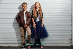 Portrait of two teenage school children on a garage door background in a city park street. stock photography
