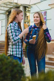 Portrait of two teenager girls standing together eating ice cream Stock Photos