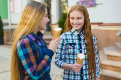 Portrait of two teenager girls standing together eating ice cream Stock Photography