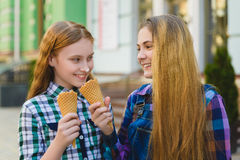 Portrait of two teenager girls standing together eating ice cream Royalty Free Stock Photography