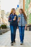 Portrait of two teenager girls standing together eating ice cream Royalty Free Stock Images