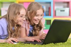 Teenagers sisters using laptop royalty free stock photography