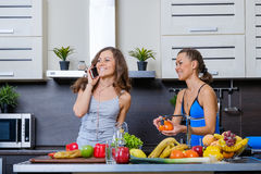 Portrait of Two twin sisters having fun in the morning preparing breakfast Stock Photos