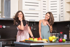 Portrait of Two twin sisters having fun in the morning preparing breakfast Royalty Free Stock Images