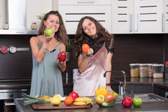 Portrait of Two twin sisters having fun in the morning preparing breakfast Royalty Free Stock Photo