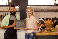 Portrait of two waiters holding a board written open Royalty Free Stock Photos