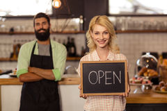 Portrait of two waiters holding a board written open Royalty Free Stock Image