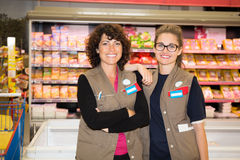 Portrait of two woman shop assistants in a supermarket. Portrait of two women shop assistants in a supermarket royalty free stock photos