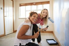 Portrait Of Two Women Decorating Room In New Home Painting Wall stock image